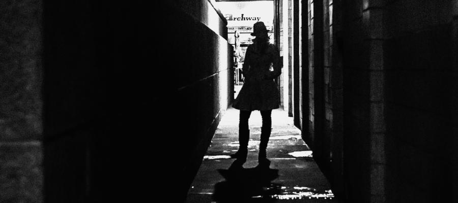 Gwen Gween standing in a dark alley wearing a trench coat and hat, hip cocked.